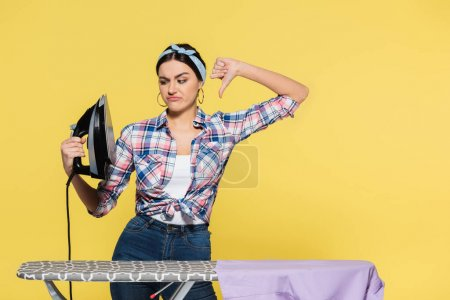 Woman holding iron and showing dislike near board with clothes isolated on yellow