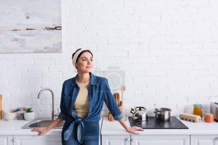 Smiling housewife in denim shirt sanding near kitchen worktop