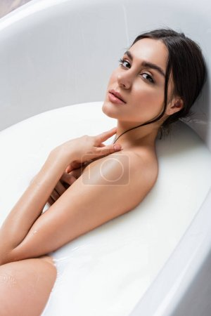 sensual woman in milk bath touching neck while looking at camera
