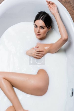 seductive woman looking at camera while covering breast in milk bath