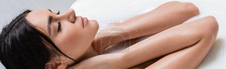young woman touching neck while relaxing in milk bath, banner
