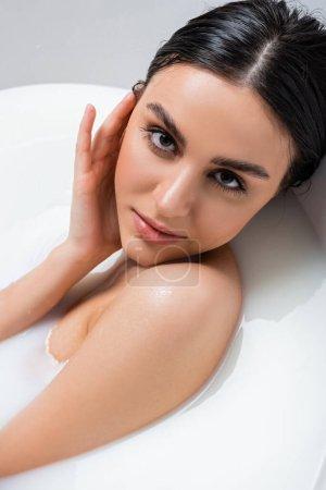 młoda kobieta dotykając twarzy i patrząc w aparat podczas kąpieli w mleku