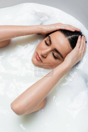 young woman with closed eyes relaxing in milk bath and touching wet hair