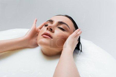 sensual woman touching wet hair while enjoying milk bath