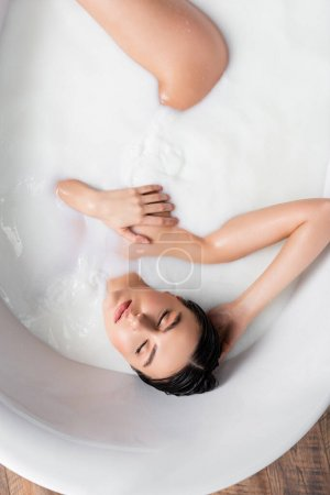 Photo for Top view of sensual woman covering breast while taking milk bath - Royalty Free Image