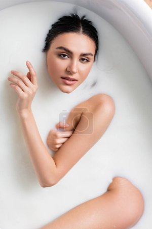 top view of pretty woman relaxing in bath with milk and looking at camera
