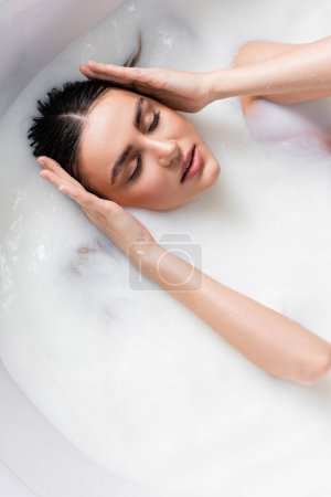 Photo for Overhead view of sensual woman touching hair while bathing in milk - Royalty Free Image