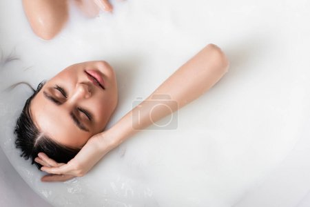 top view of woman with closed eyes relaxing in bath with milk