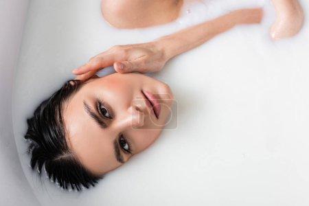 Ansicht von oben: Junge Frau berührt Gesicht beim Milchbad