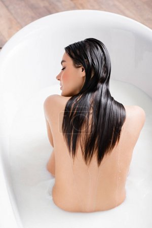 Photo for Young woman with wet hair relaxing in milk bath - Royalty Free Image