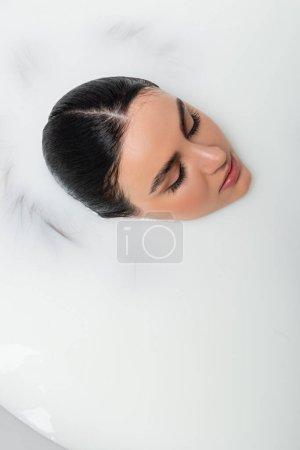 vista aérea de la mujer con los ojos cerrados tomando baño de leche