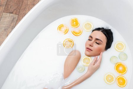 pretty woman touching face while bathing in milk with sliced citrus fruits