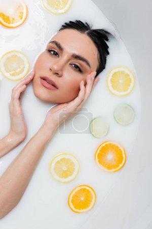 Foto de Mujer joven tocando la cara y mirando a la cámara en el baño de leche con rodajas de cítricos - Imagen libre de derechos