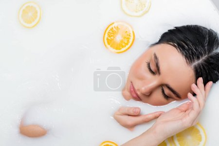 top view of pretty woman with closed eyes taking milk bath with lemon and orange slices