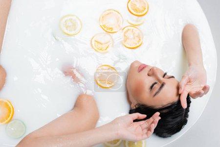 Ansicht einer Frau mit geschlossenen Augen im milchigen Bad mit frischen Zitrusfrüchten