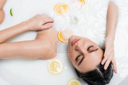 vue du dessus de la jeune femme dans le bain avec du lait et des agrumes tranchés