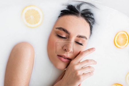 top view of young woman enjoying bathing in milk with fresh, sliced citruses