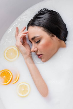 sensual woman relaxing with closed eyes in milk bath with orange and lemon slices