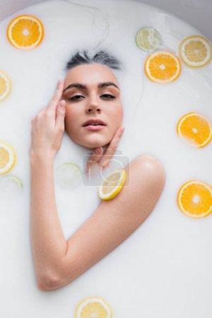 sinnliche Frau blickt in die Kamera, während sie in Milch mit Zitrusscheiben badet