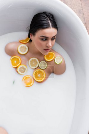 Photo for Young woman taking milk bath with sliced lemon, lime and orange - Royalty Free Image