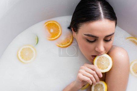 pretty woman biting slice of fresh lemon while relaxing in milk bath