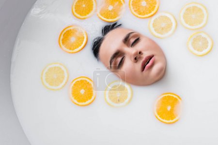 top view of female face in milky bath with sliced lemon and orange