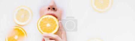 top view of woman holding orange slice in milk bath, banner