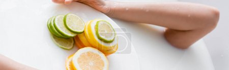 partial view of woman taking milk bath near slices of fresh citruses, banner