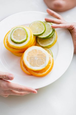 cropped view of woman holding plate with sliced citruses while taking milk bath