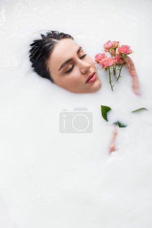 junge Frau entspannt sich im Milchbad mit rosa Rosen