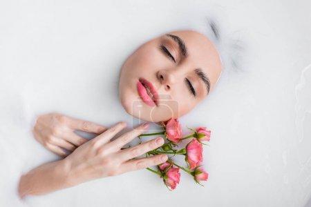 Photo pour Vue du dessus de la jeune femme aux roses roses prenant un bain laiteux - image libre de droit
