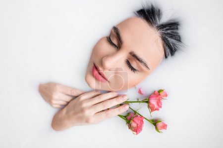 Photo for Young woman with closed eyes and pink roses bathing in milk - Royalty Free Image