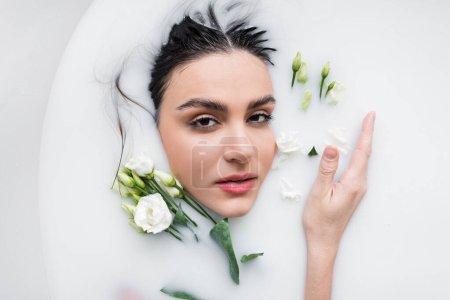 femme sensuelle regardant la caméra tout en prenant un bain de lait avec des fleurs d'eustomie