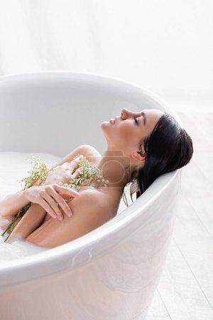 woman with closed eyes taking milk bath with gypsophila flowers