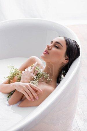 mujer bonita con los ojos cerrados y flores blancas, minúsculas sentadas en la bañera con leche