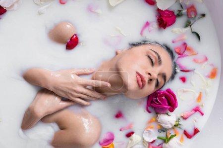 seductora mujer tocando el cuello mientras toma baño de leche con pétalos de rosa