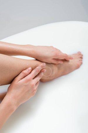 Teilbild einer Frau, die beim Baden in Milch Bein berührt