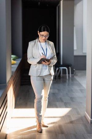 Mujer de negocios asiática en anteojos escribiendo en cuaderno en la oficina
