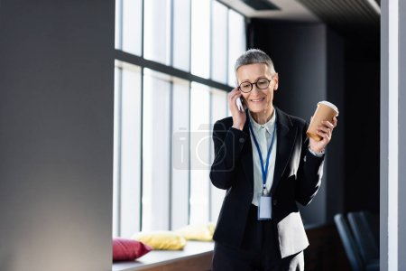 Photo for Mature businesswoman with coffee to go smiling and talking on smartphone - Royalty Free Image