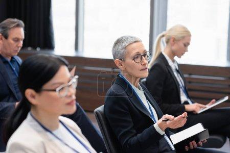 Madura mujer de negocios con pluma y portátil hablando durante la conferencia