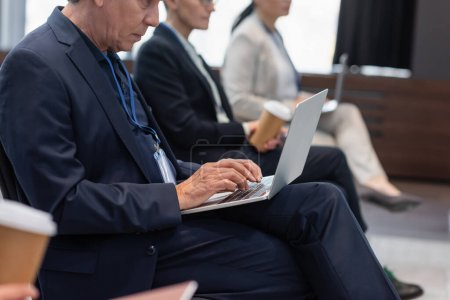 Cropped view of businessman using laptop near blurred colleagues during seminar