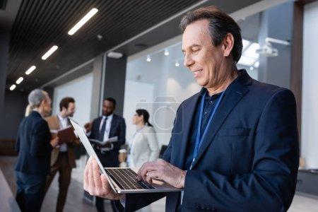 Photo pour Homme d'affaires souriant utilisant un ordinateur portable dans le hall de bureau - image libre de droit