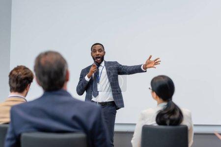 Orador afroamericano hablando cerca de gente de negocios borrosa durante el seminario