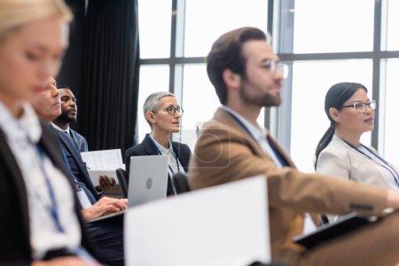 Photo pour Femme d'affaires mature regardant loin près de collègues multiethniques pendant le séminaire - image libre de droit