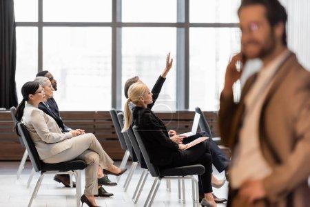 Photo pour Interracial hommes d'affaires assis dans la salle de conférence près flou homme d'affaires - image libre de droit