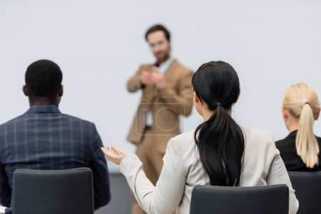 Businesswoman sitting in conference room near interracial colleagues and blurred speaker