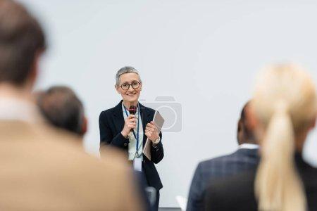 Photo pour Enthousiaste haut-parleur d'âge moyen avec dossier papier parlant pendant la réunion d'affaires - image libre de droit