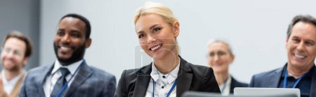 Photo for Smiling businesswoman looking away near multiethnic colleagues in conference room, banner - Royalty Free Image