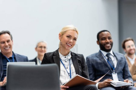 Alegre empresaria con carpeta de papel sentada cerca de colegas multiétnicos durante el seminario