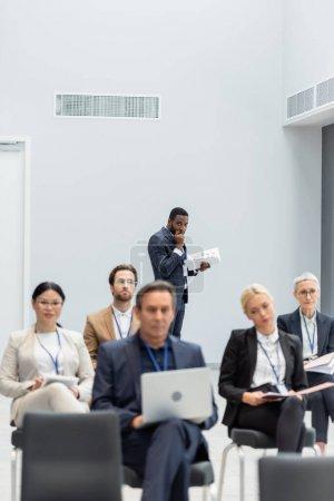 Photo pour Homme d'affaires afro-américain tenant des documents près des hommes d'affaires interraciaux flous dans la salle de conférence - image libre de droit